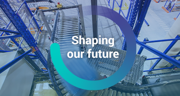 The words, 'Shaping our Future' inside a circle graphic overlayed on top of an image of a moving pallet on a conveyor belt