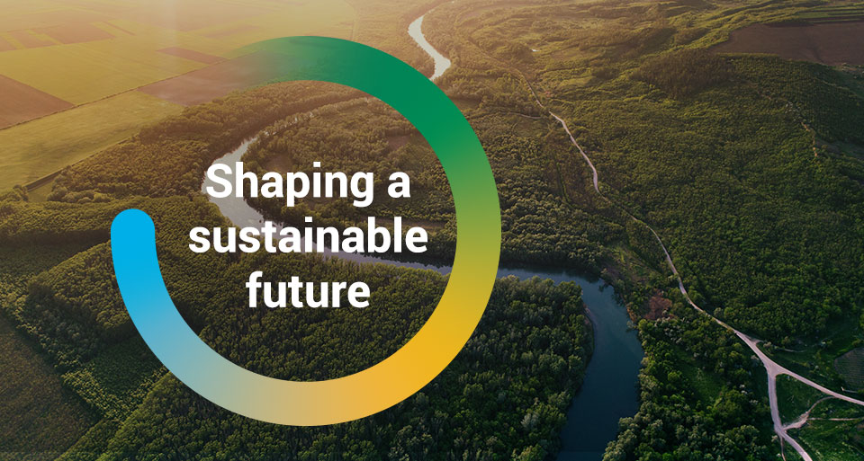 The wordAn aerial photograph of a river with the words Shaping a Sustainable Future inside a colourful circles, 'Shaping our Future' inside a circle graphic overlayed on top of an image of a moving pallet on a conveyor belt